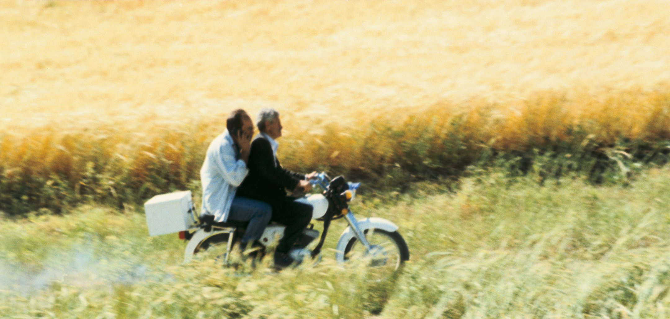 Still of Behzad Dorani and the doctor on a motorbike in a still from 'The Wind Will Carry Us' (1999, Copyright MK2)
