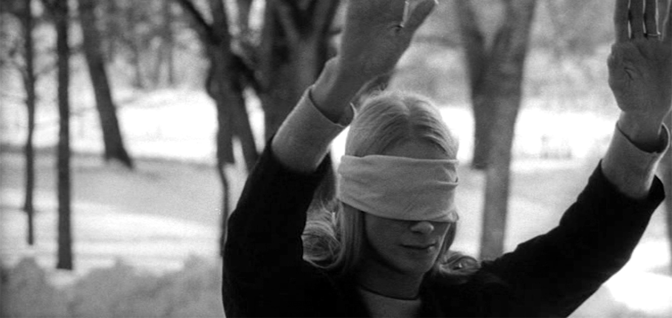 Ingrid Thulin as Irene, blindfolded with her arms out in a forest in a still from Night Games (1966)