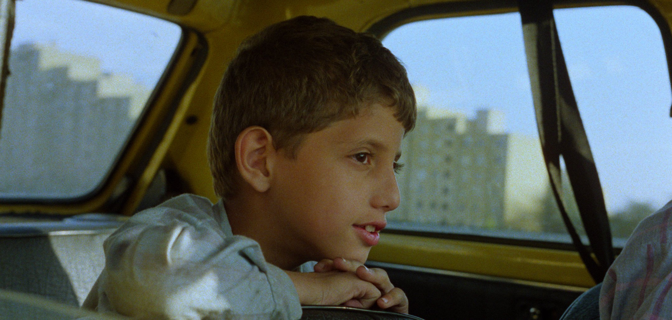 A young boy in the back of a car in a still from 'And Life Goes On' (1992)