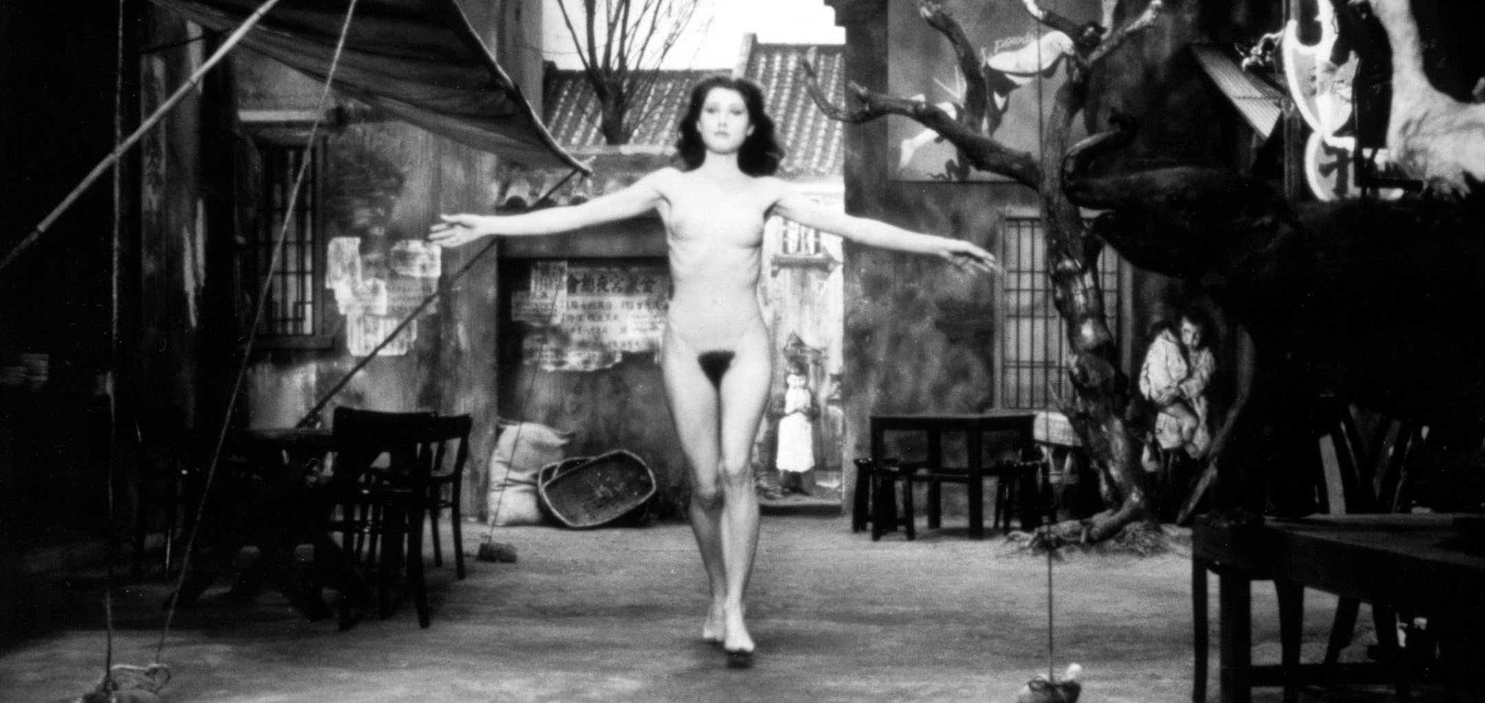 A nude woman with arms outstretched in a still from 'The Fruits of Passion' (1981)