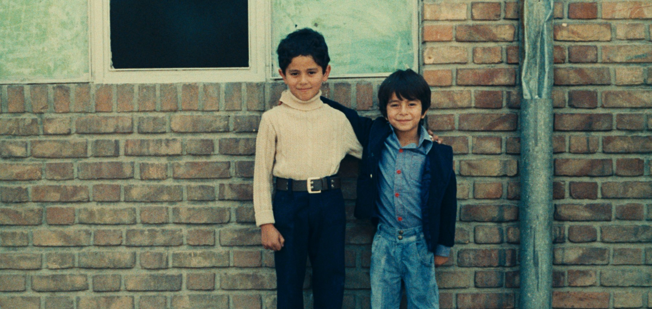 Still of two boys standing against a brick wall in a still from 'Two Solutions For One Problem' (1975) (c) Kanoon