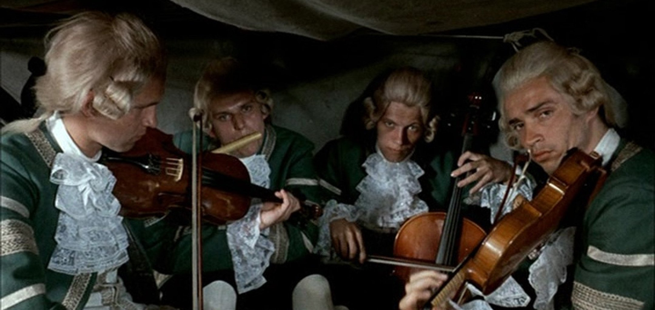 4 violinists play in the back of a carriage in a still from 'Pacho, the Thief of Hybe' (1976)