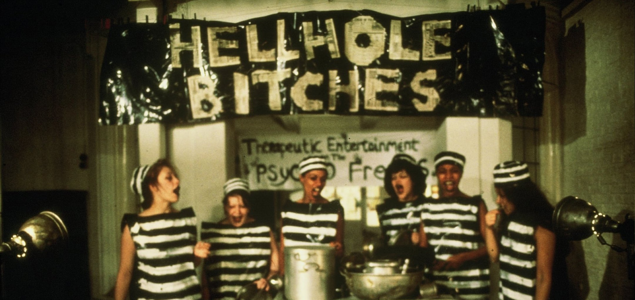 6 prisoners standing in front of cooking pots with a banner behind them reading 'Hellhole Bitches' - still from Scrubbers (1982)