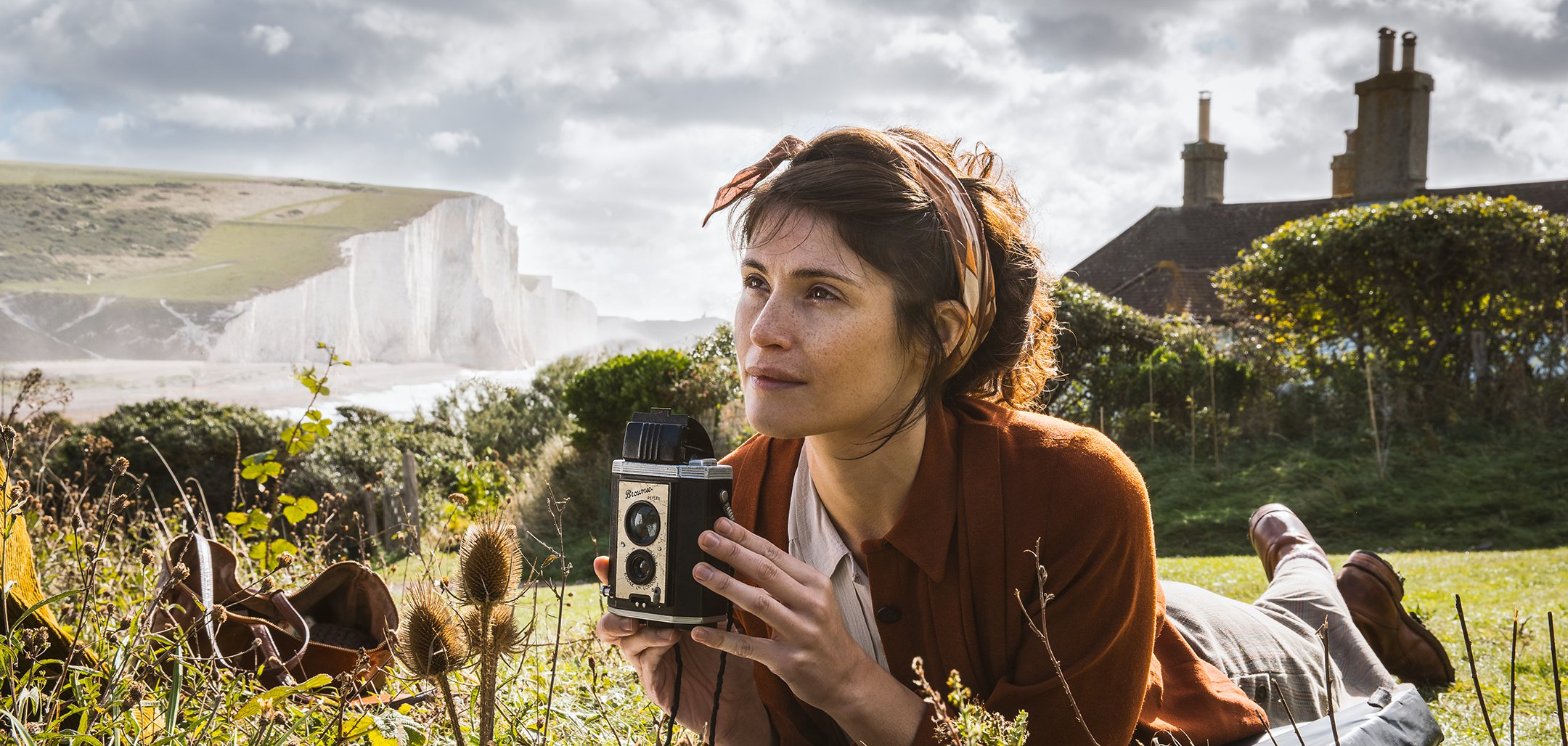 Gemma Arterton lying in a field with a camera in a still from Summerland (2020)