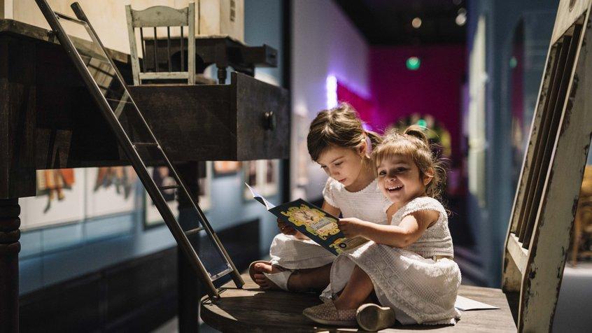 Kids sit on an oversized chair in ACMI's Wonderland exhibition