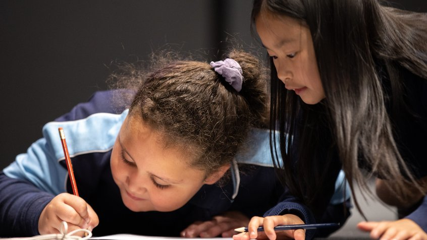 A school group peers through the multicolour window at ACMI