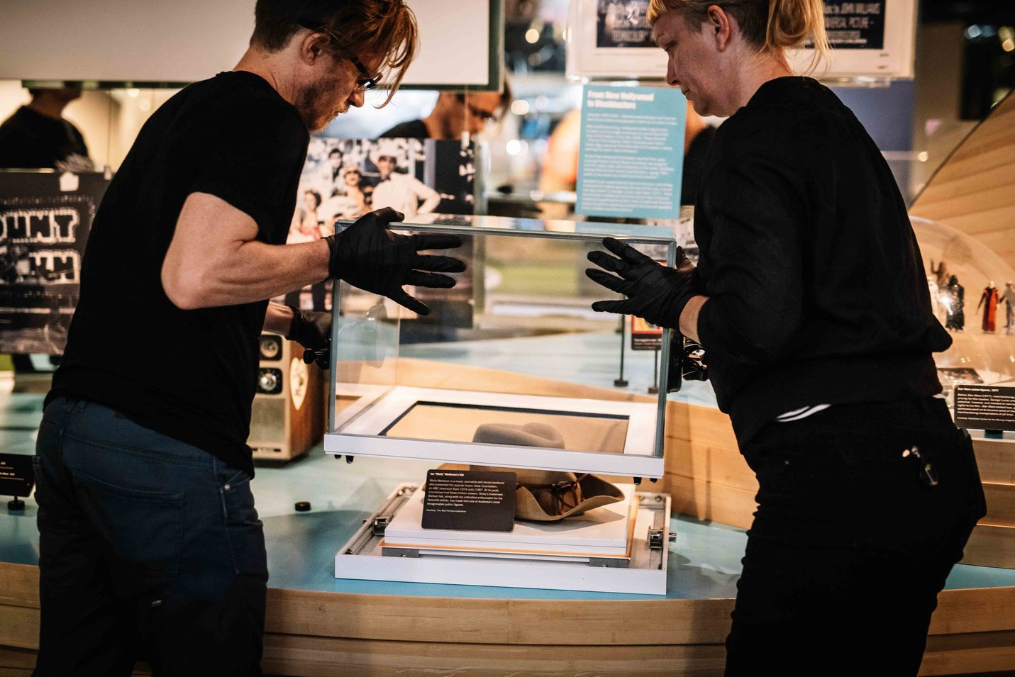 ACMI exhibition technicians remove perspex covers to remove Molly Meldrum's hat Photographer- Phoebe Powell
