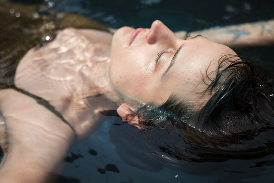 Closeup of person's face with eyes closed as they float in a floatation tank