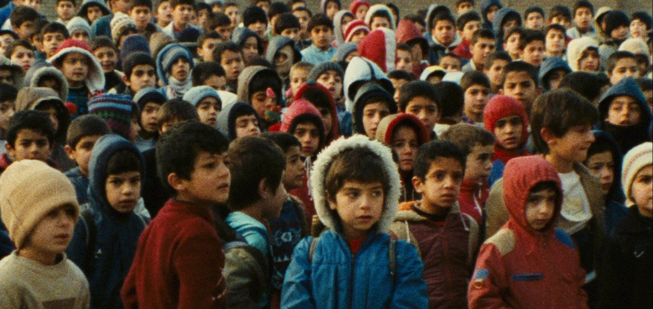A crowd of kids in winter clothes in a still from 'Homework' (1989)