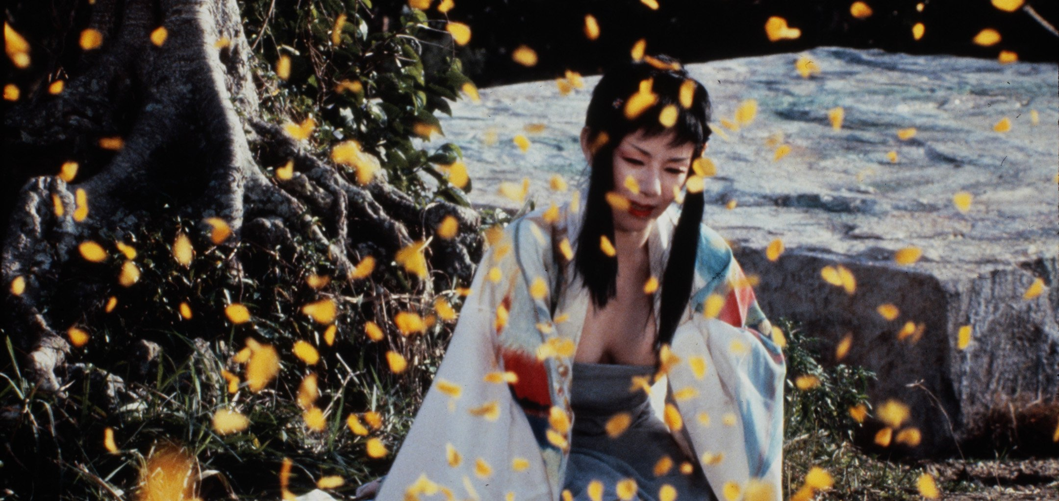 A woman in a kimono kneeling and crying as leaves fall in the foreground - still from 'Farewell to the Ark' (1984)