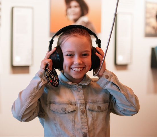 A young girl listens to an audio description in the Moving Australia section of The Story of the Moving Image (Phoebe Powell)