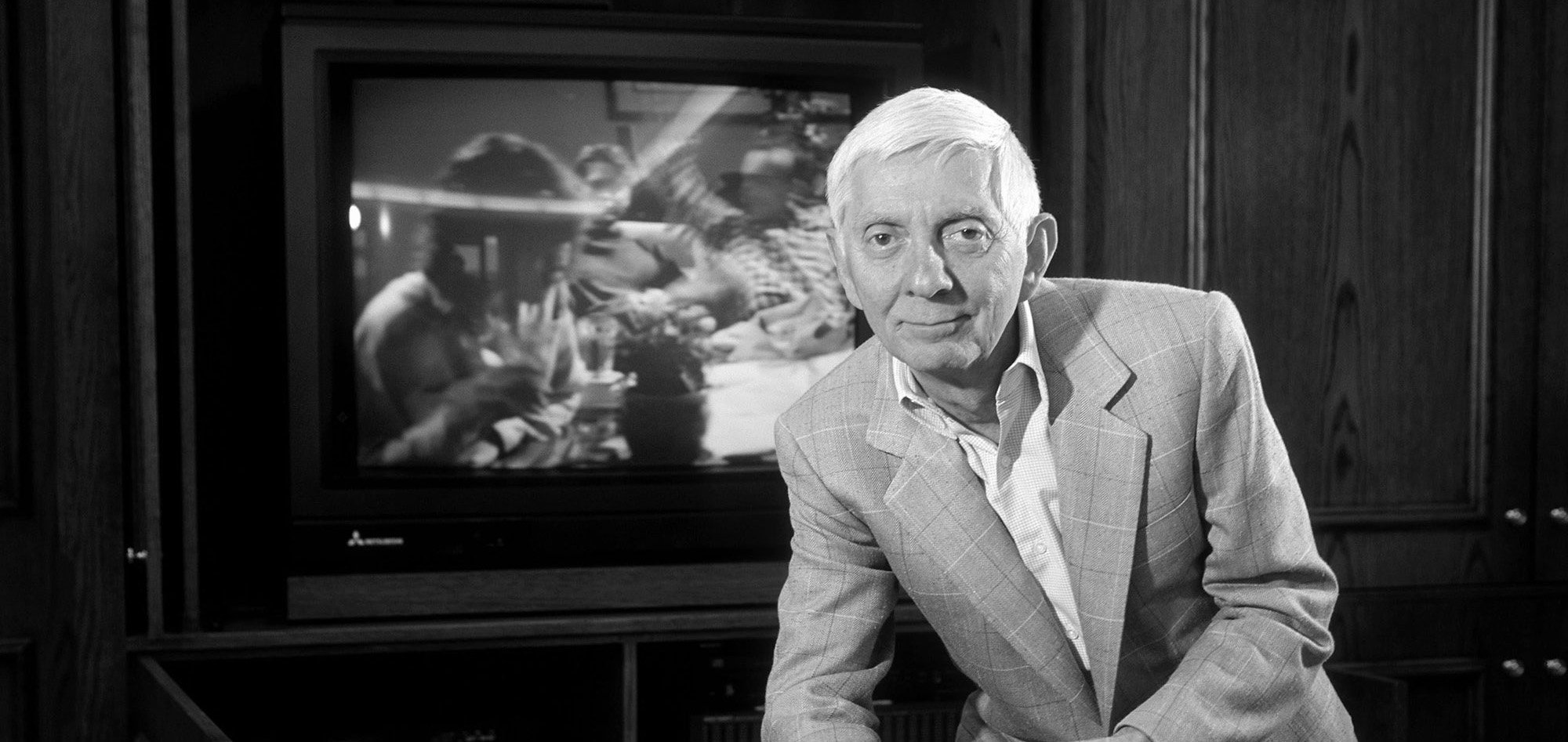 Aaron Spelling holding a remote control in front of a TV set