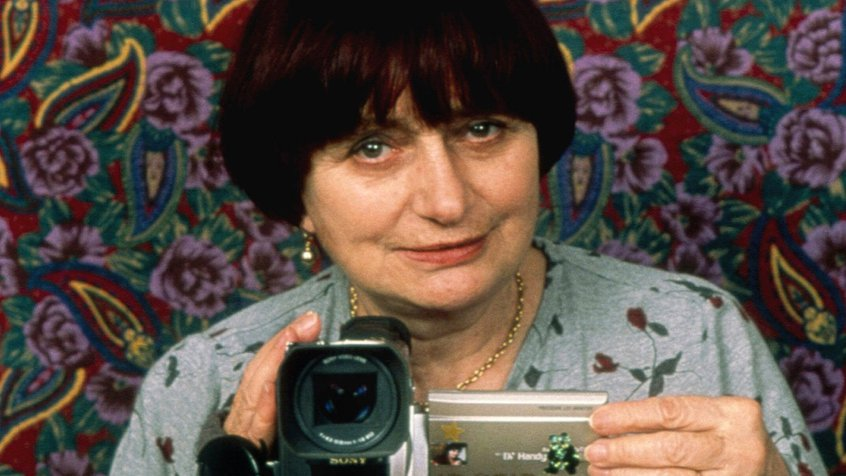 Agnès Varda resting a camcorder on top of a painting with a floral background