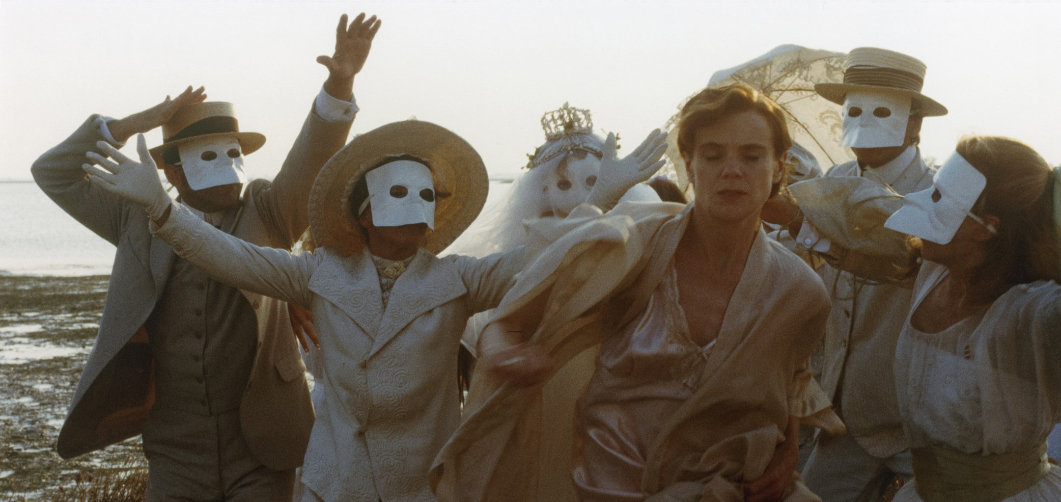 Stina Ekblad in a white nightgown surrounded by figures in white Venetian masks in a still from Amorosa (1985)