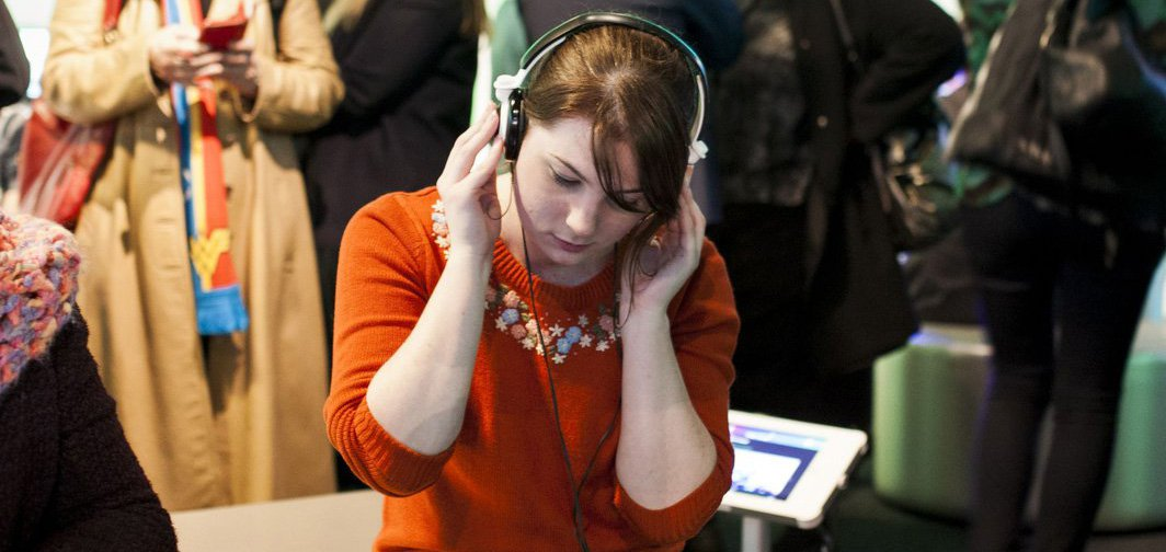 A young woman wearing headphones and testing out a screen work at the ACMI + RMIT Audience Lab. Photograph by Charlie Kinross