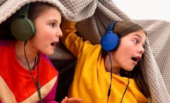 Kids playing the Audioplay app with headphones under a blanket