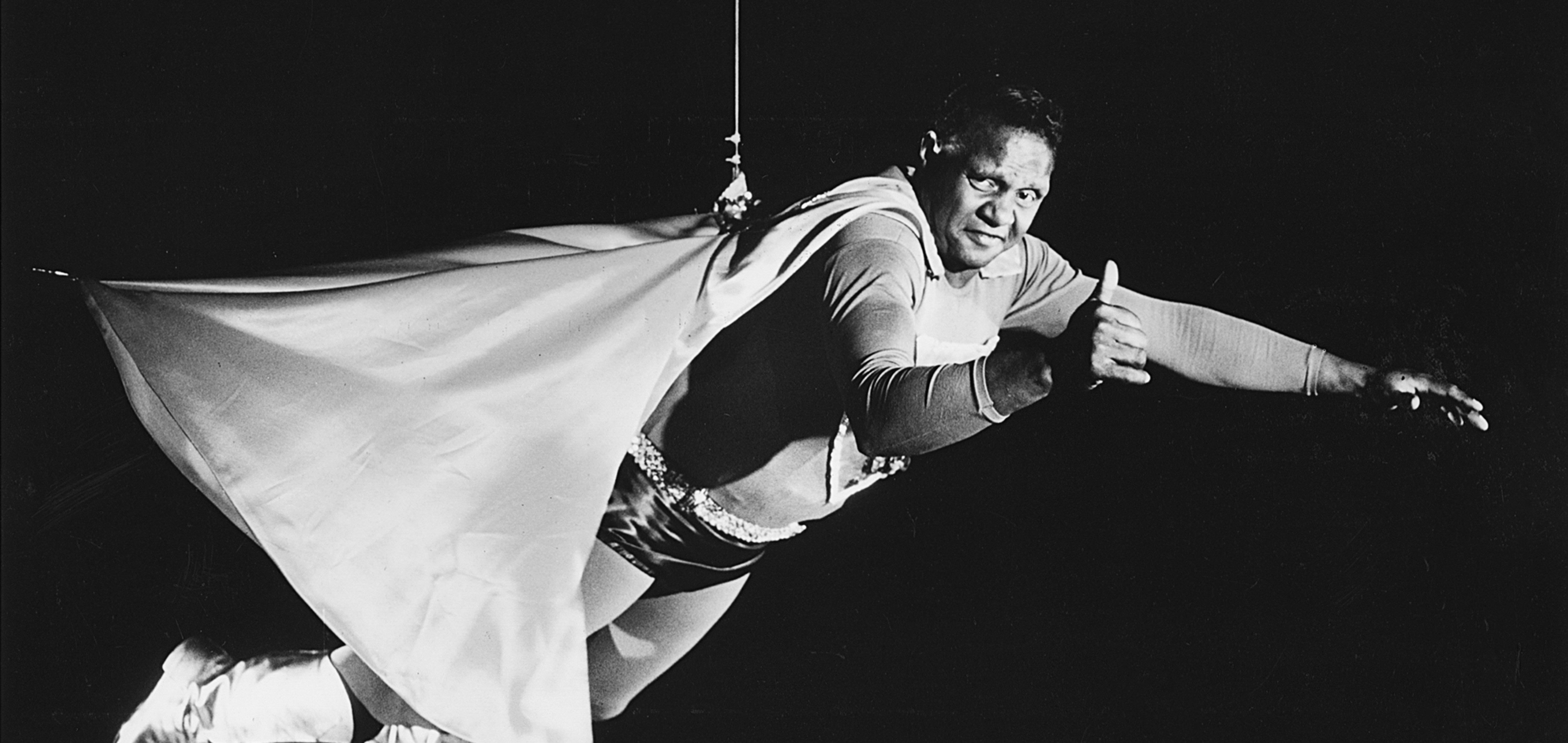Zac Martin in a superhero costume being held up by a wire in a still from 'Basically Black' (1973)