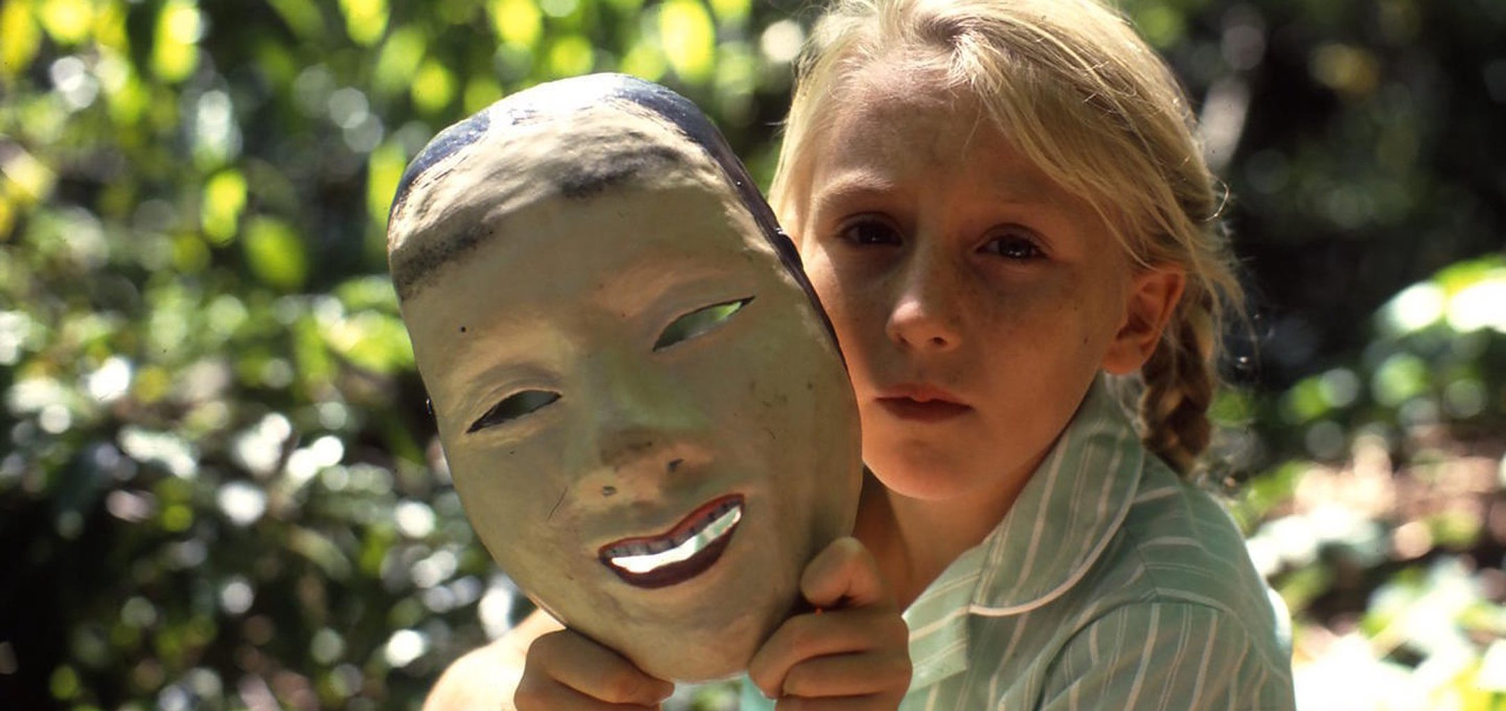 Rebecca Smart as Celia holding a mask in a still from Celia (1989)