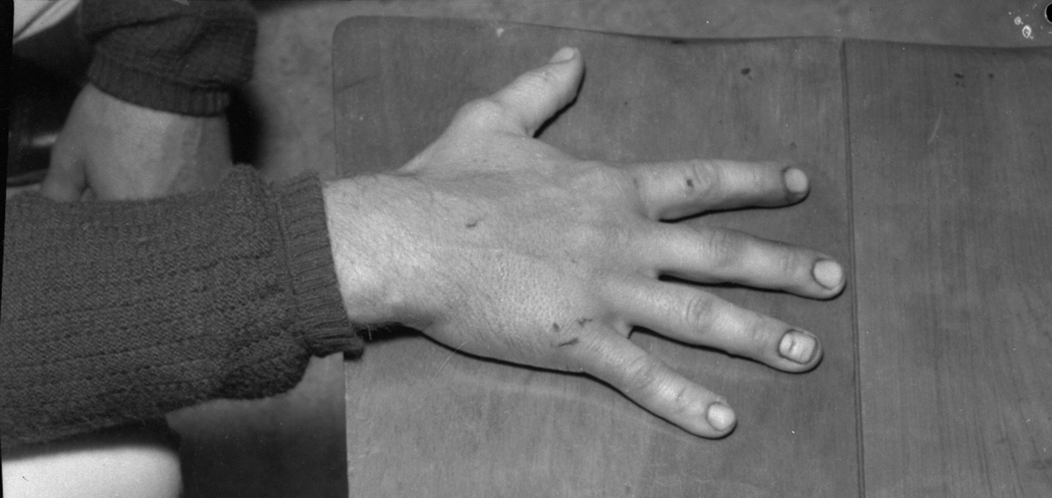 Closeup of hand - a still from Ross Gibson - head_phone_film_poems