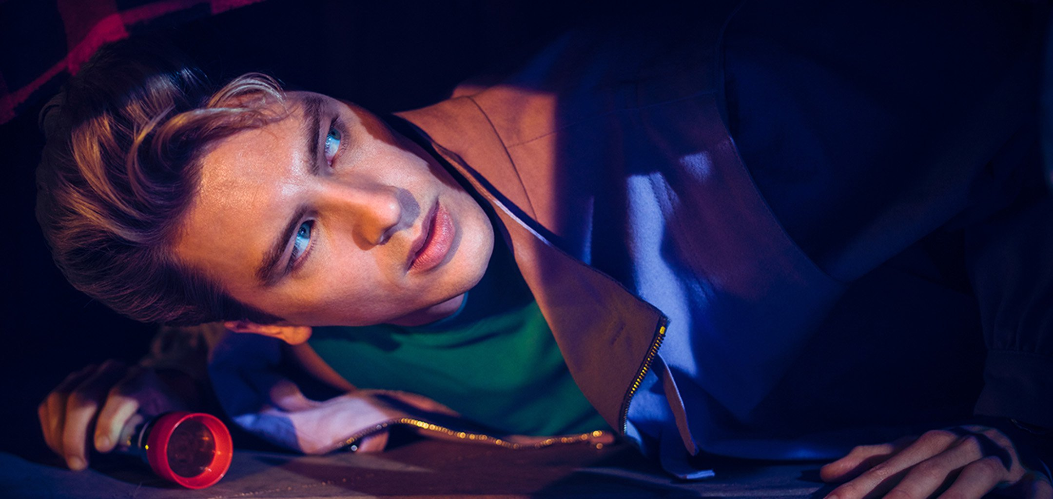 Cody Fern as Xavier Plympton checks under the bed in a still from 'American Horror Story - 1984'