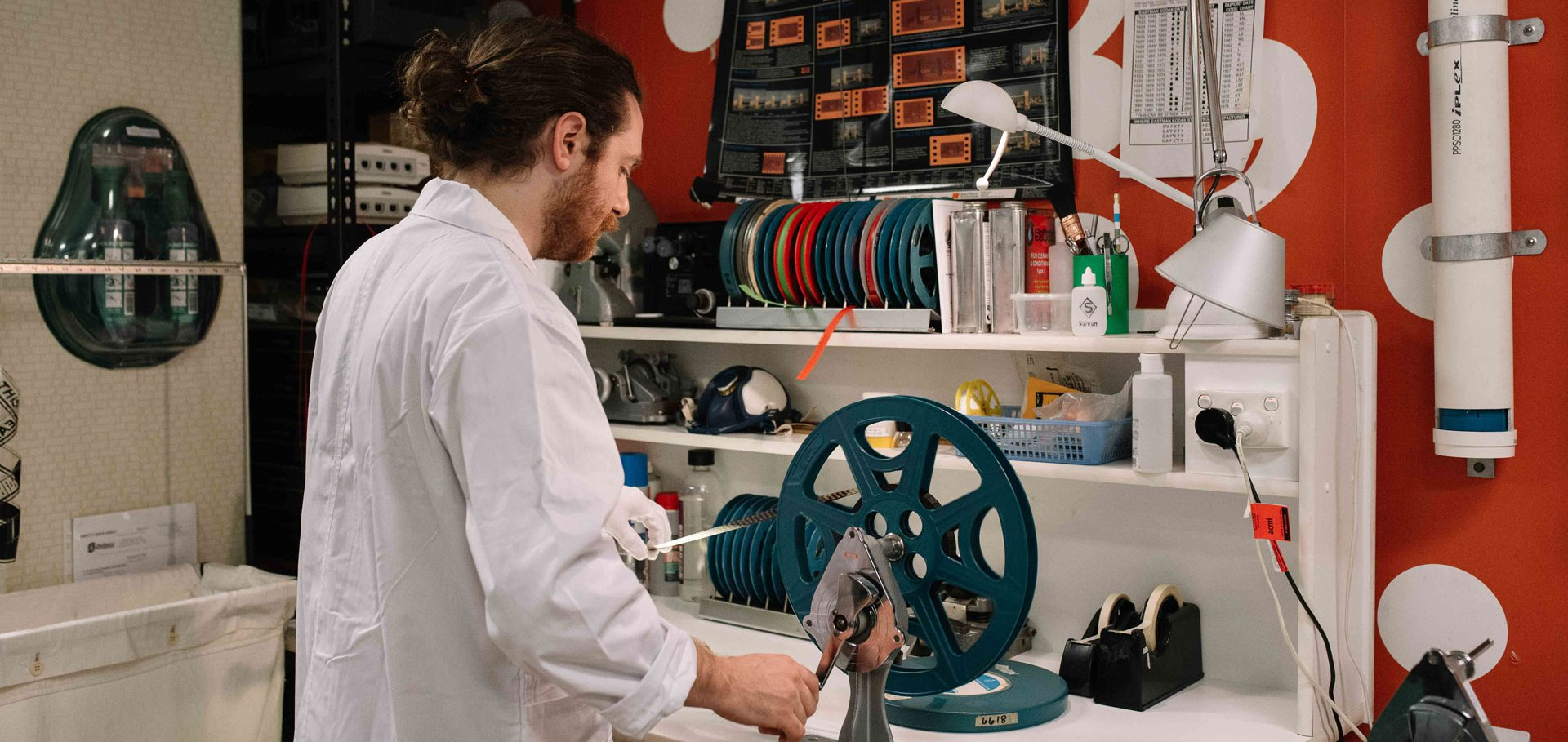 Collections technician Ben Abbott checking the condition of a 16mm film at a winding bench. Image credit: Phoebe Powell