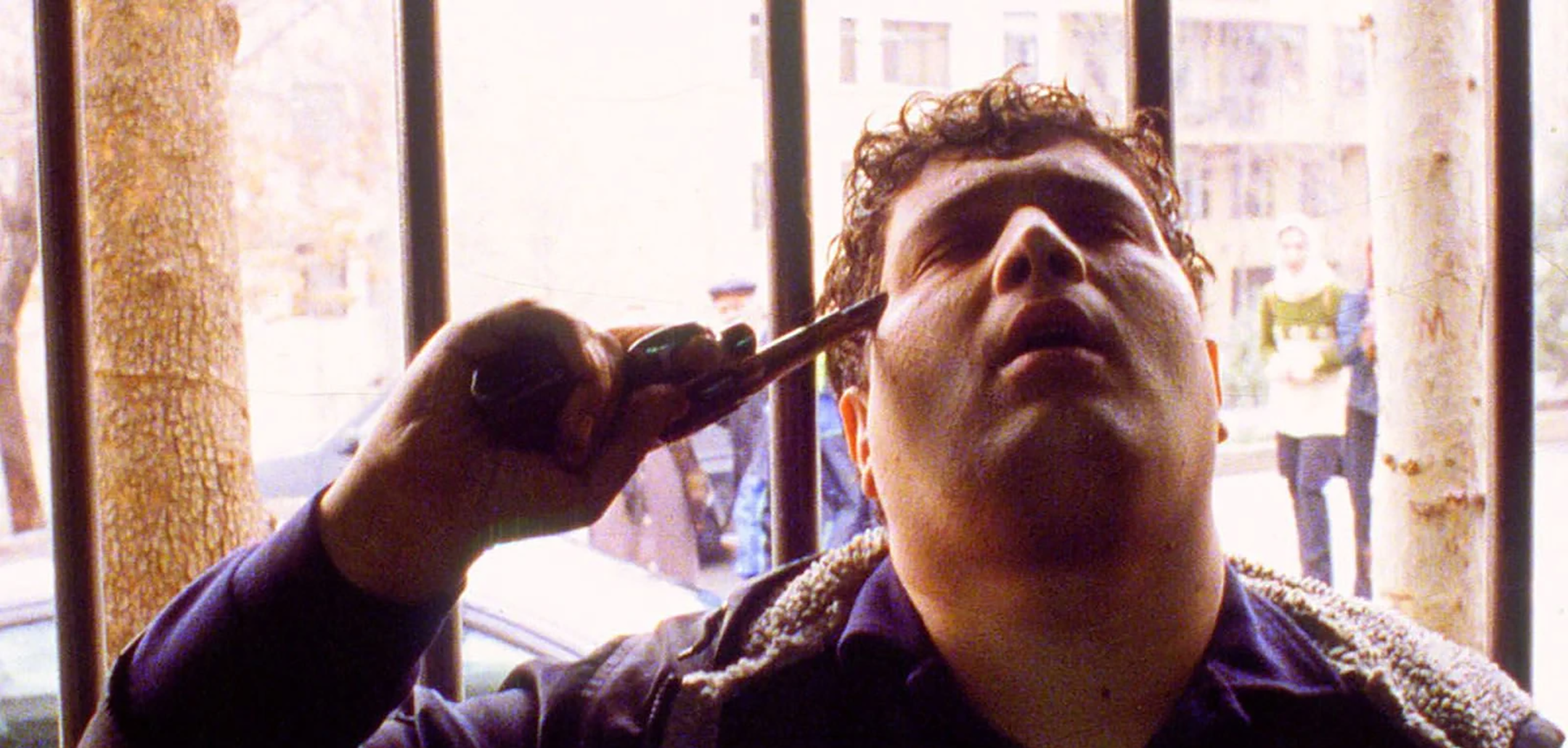 Hossain Emadeddin points a gun to his head in a still from 'Crimson Gold' (2003)