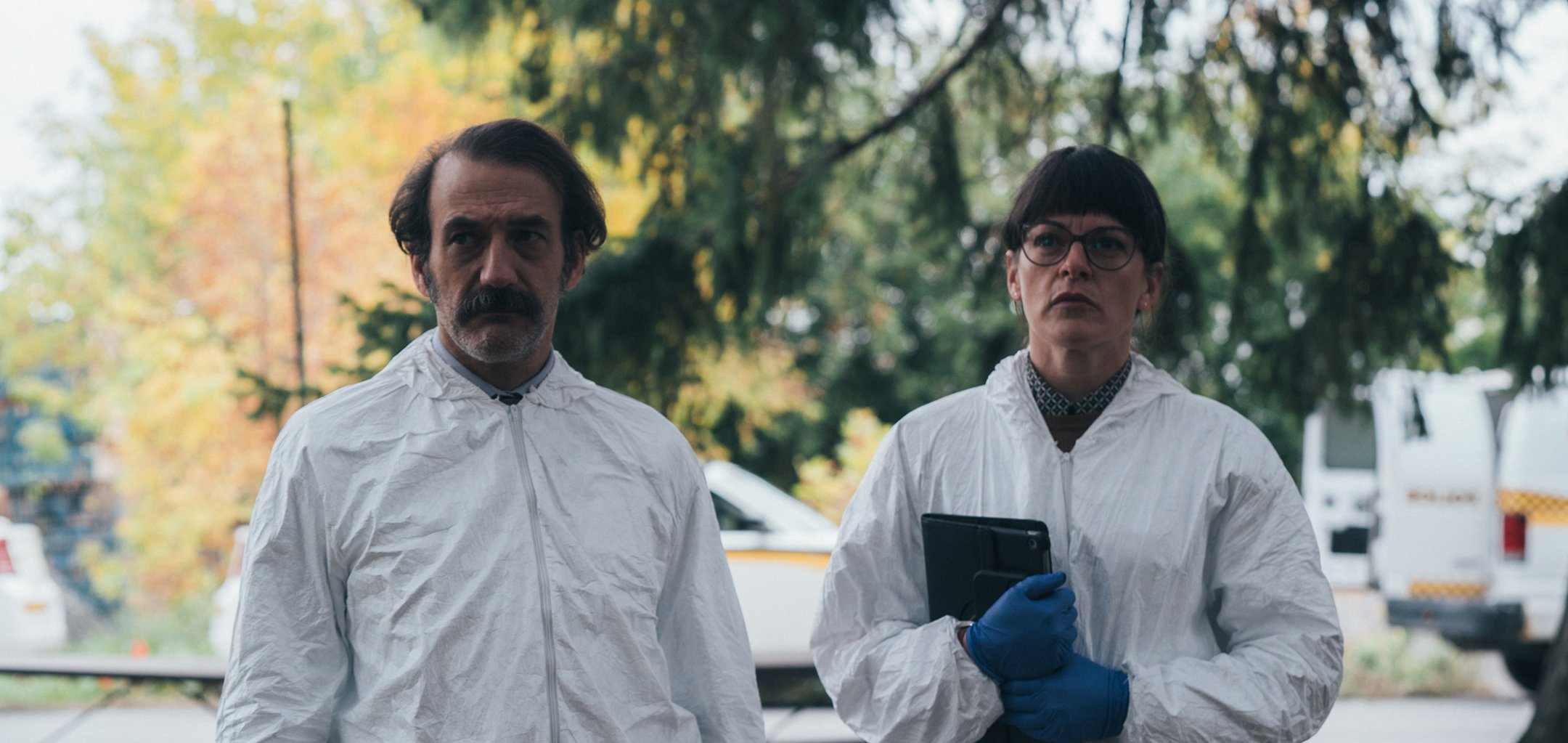 Two people in crime scene clothing in a still from 'Dark Soul '(2021) Encore International