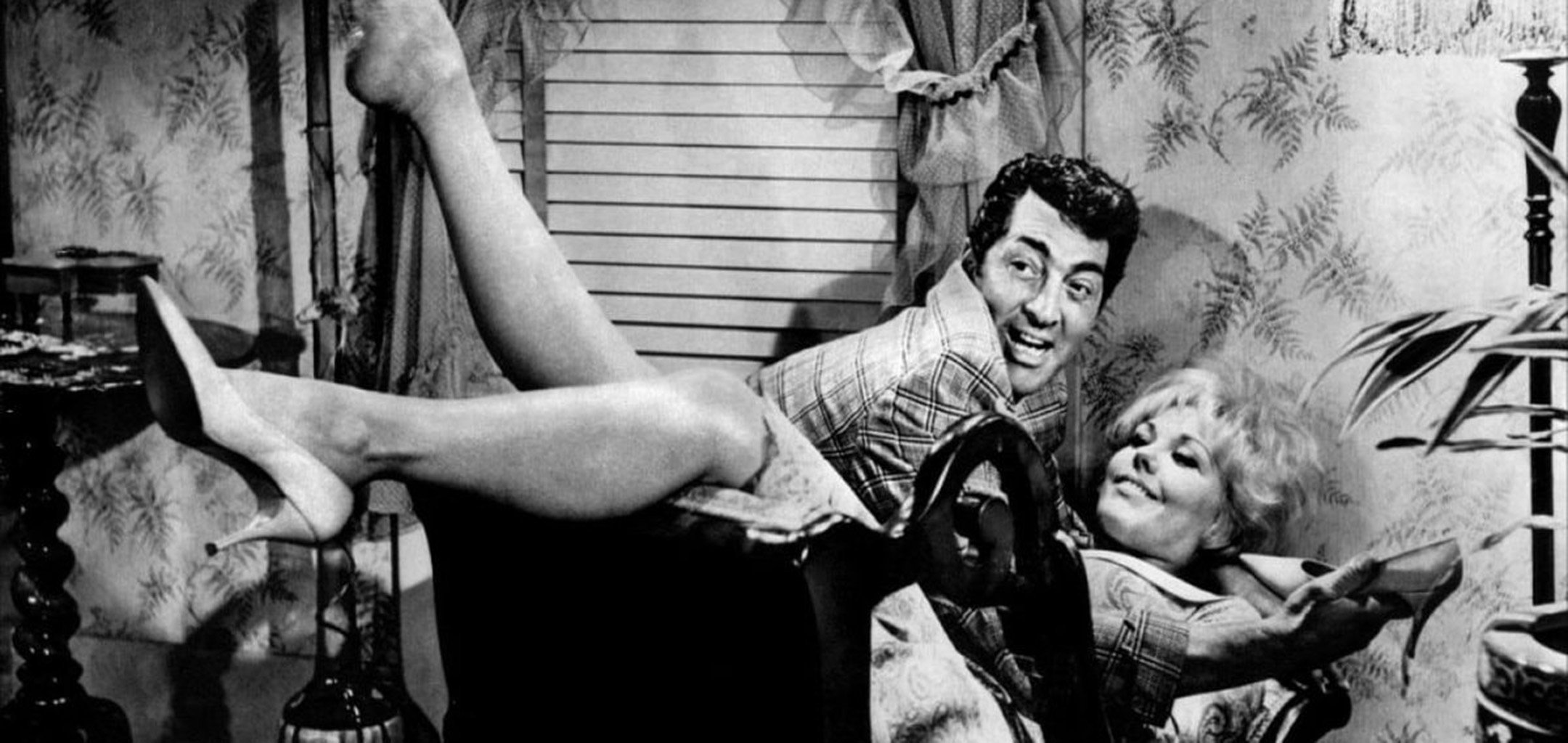 Dean Martin and Kim Novak in a wild embrace on the couch in a still from Kiss Me, Stupid (1964)