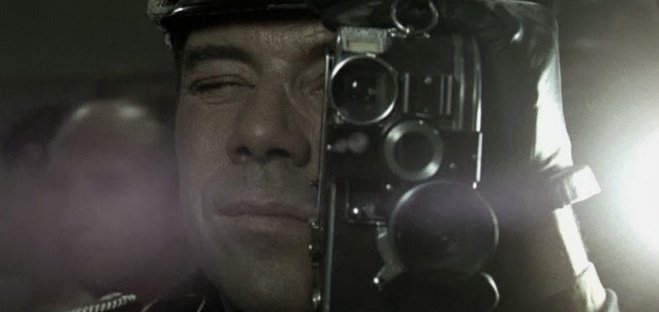 Dirk Bogarde looks through a camera in a scene from The Night Porter (1974)