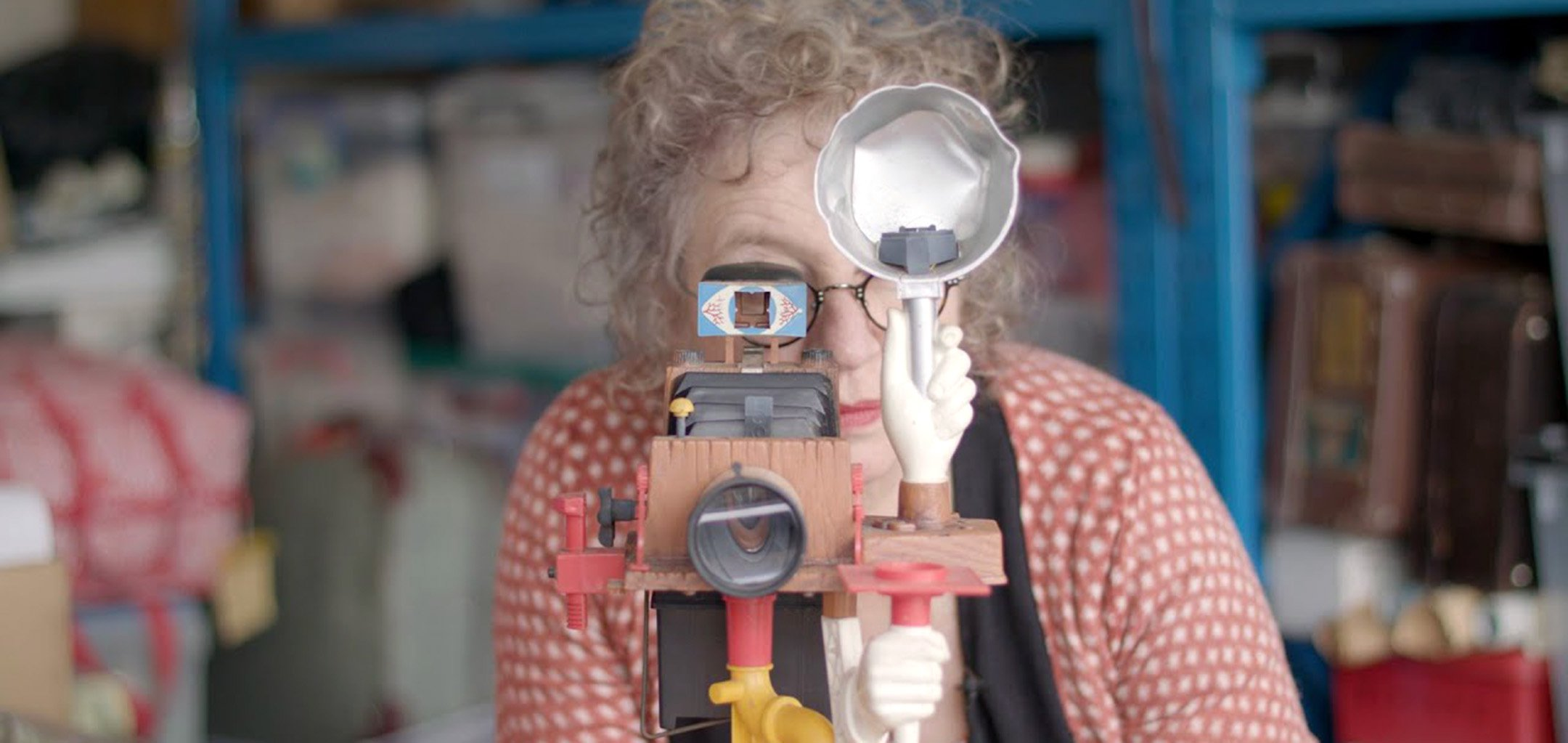 A woman (Edie Kurzer) wearing a polkadot dress looks down the lens of a camera made from disparate, colourful parts