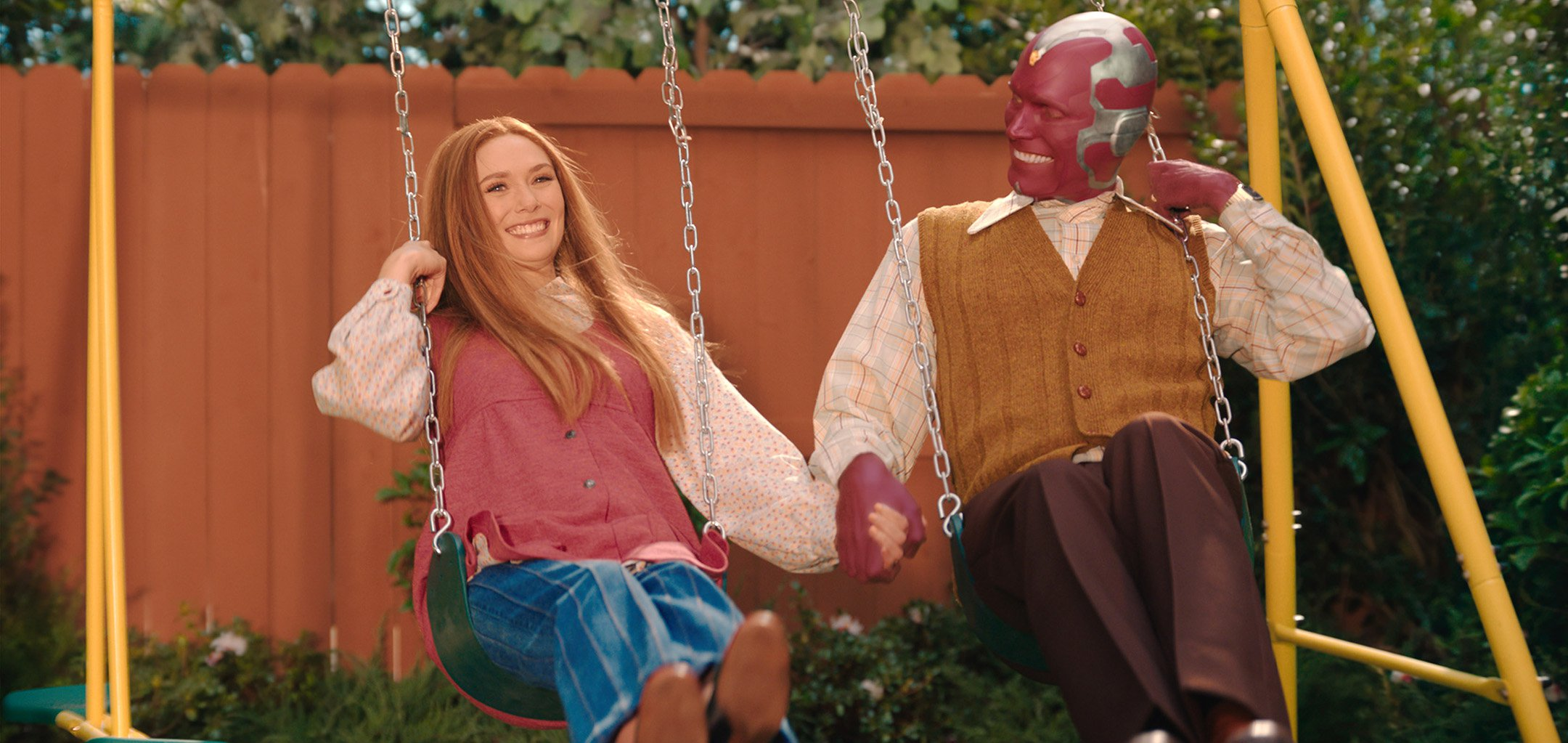 Elizabeth Olsen and Paul Bettany smilin on a swing set - still from WandaVision (2021)