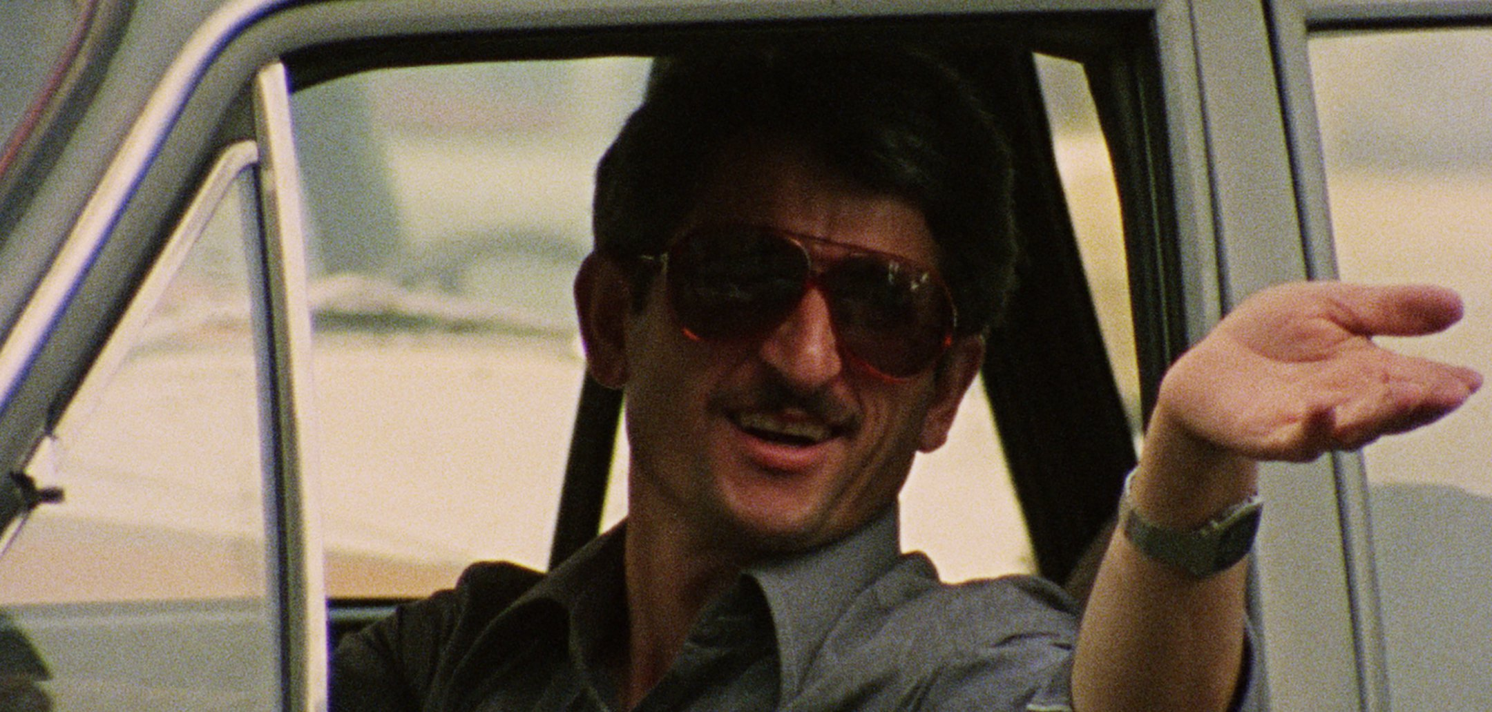 A man gestures out a car window in 'Fellow Citizen' (1983)