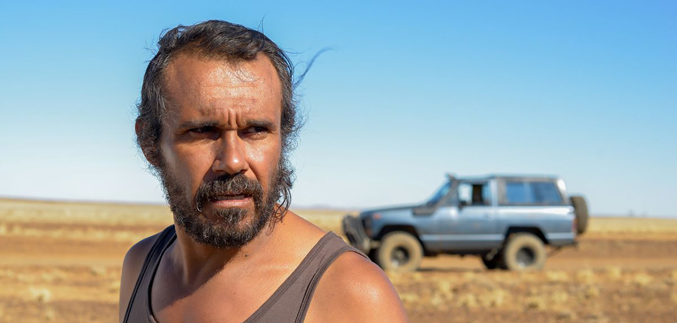 Closeup of Aaron Pedersen in the desert, in the background there is a jeep. Still from 'Goldstone' (2016)