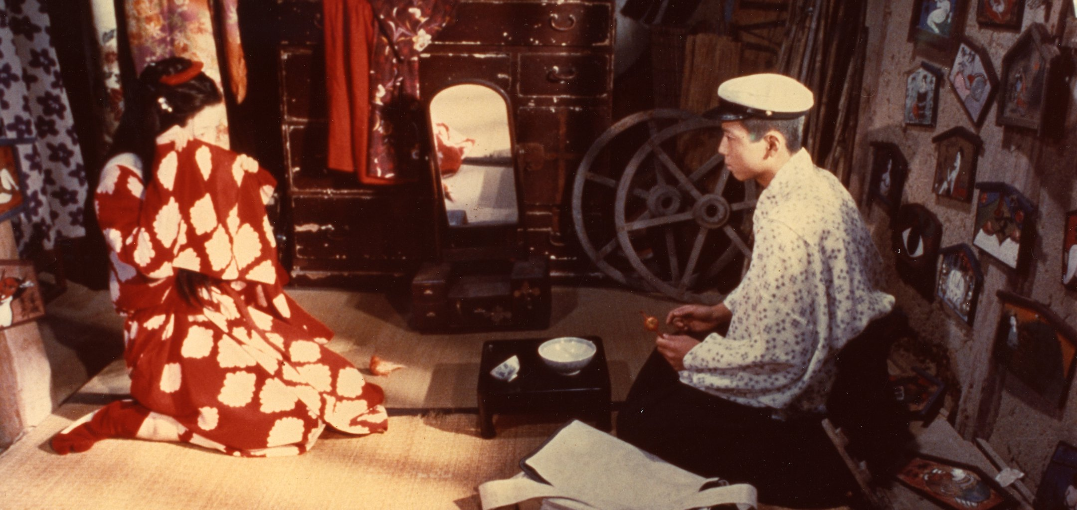A woman and a man in traditional Japanese dress kneel inside a living room in a still from Grass Labyrinth (1979)