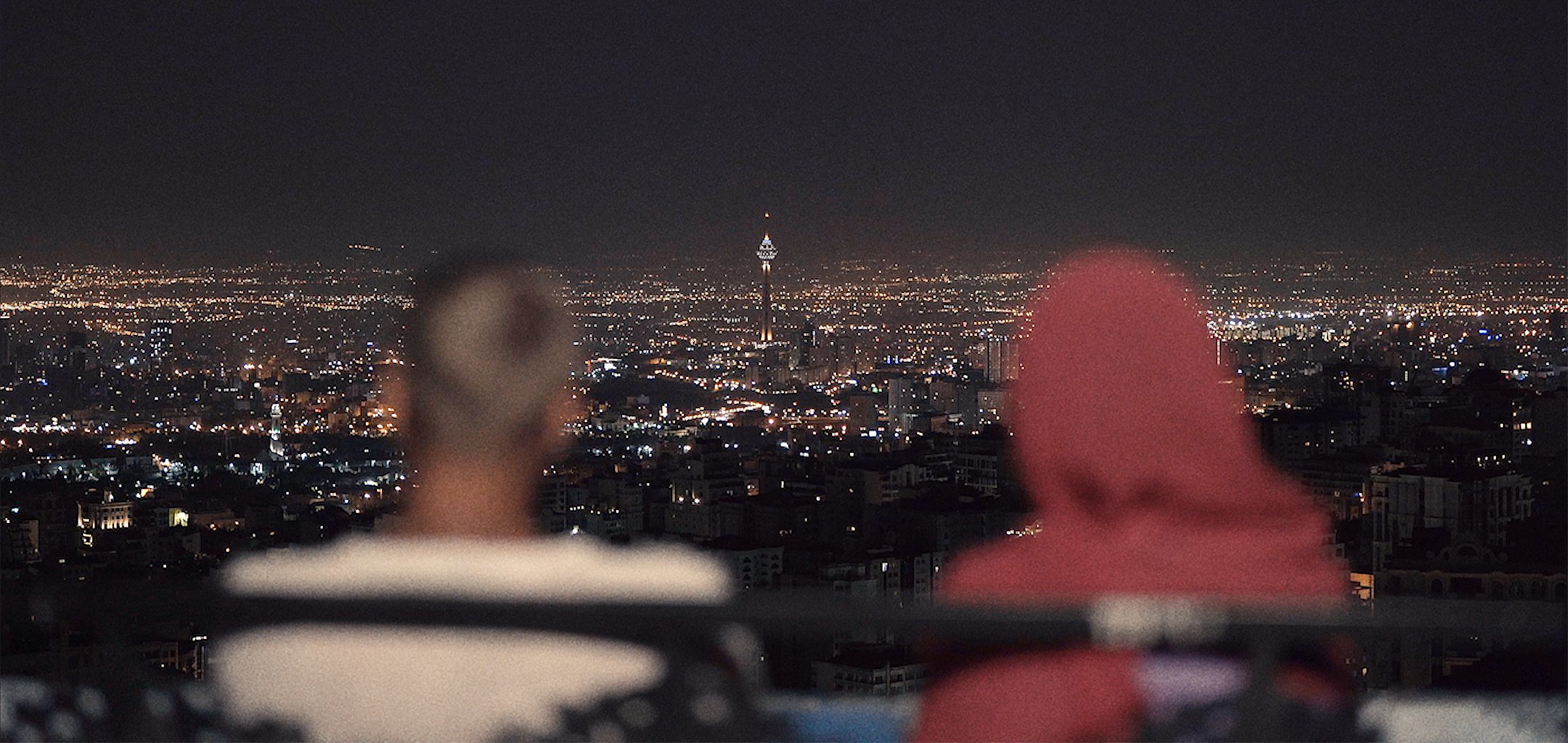 Two figures looking over a cityscape vista at night in 'Happiness' (2021) La Onde Productions