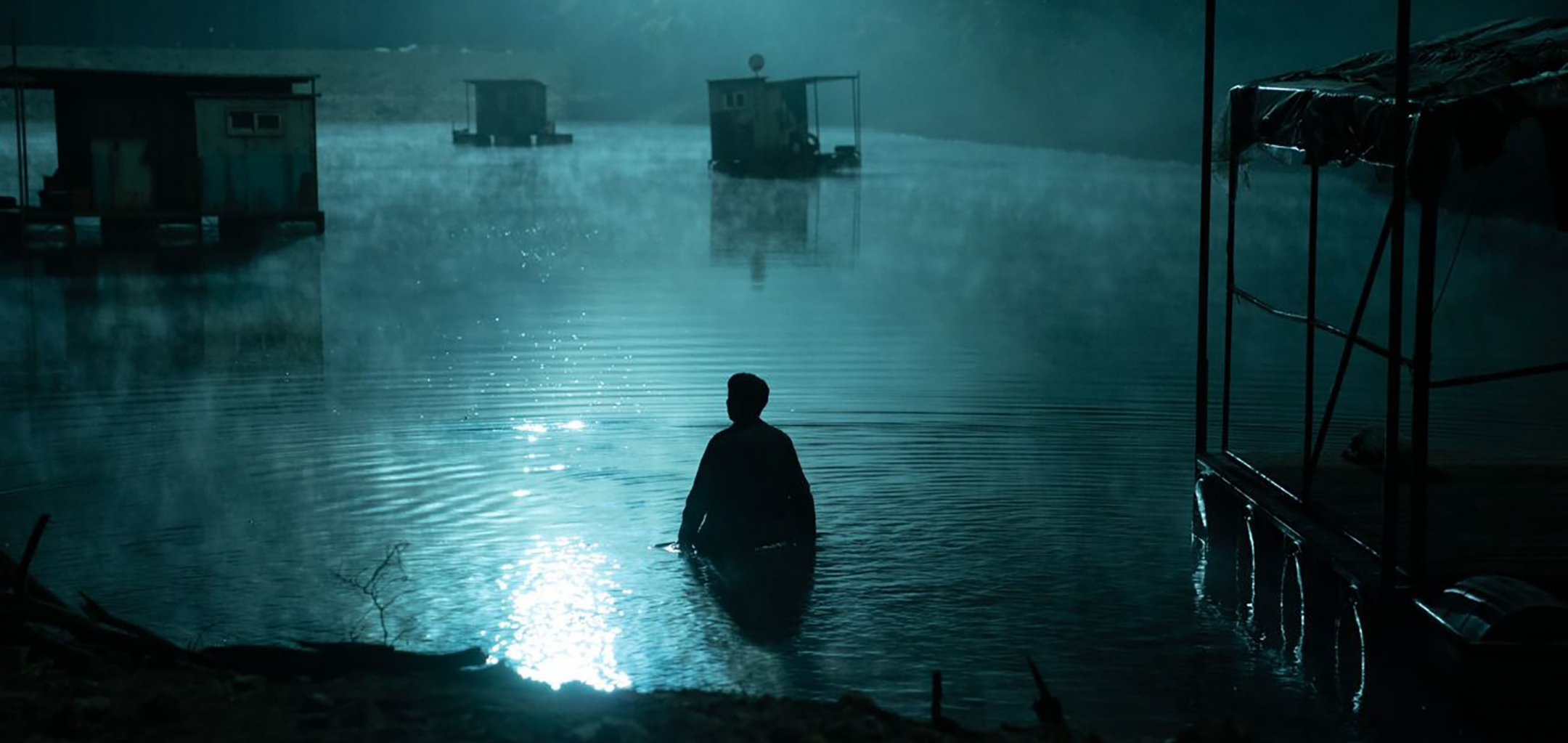 Still of silhouetted man wading in shallow foggy water from 'Hellbound' (2021) Netflix