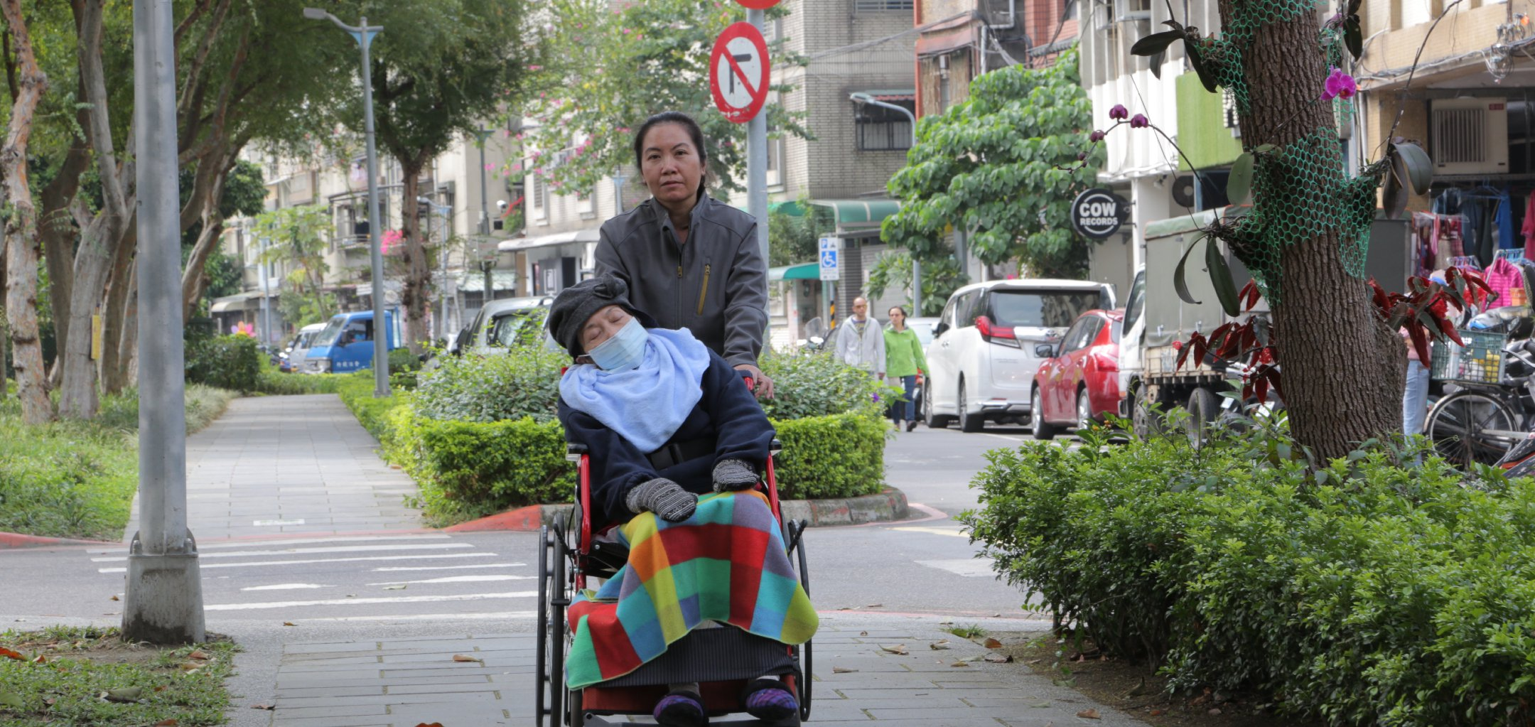 An Indonesian woman pushes an elderly person in a wheelchair in a still from 'Help is on the Way' - IFF 2021