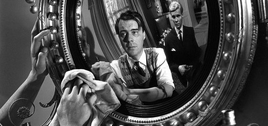 Hugo polishes a mirror with Tony looking on - Dirk Bogarde and James Fox in The Servant (1963)