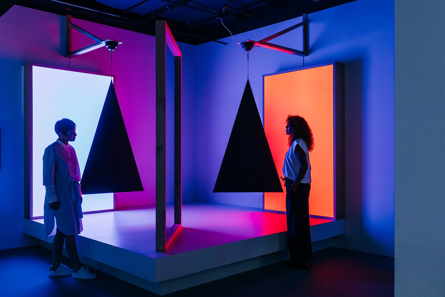 Visitors looking at Pepper's ghost effect, triangles, cyan and red, Taree Mackenzie, 2018 photograph by Gareth Sobey