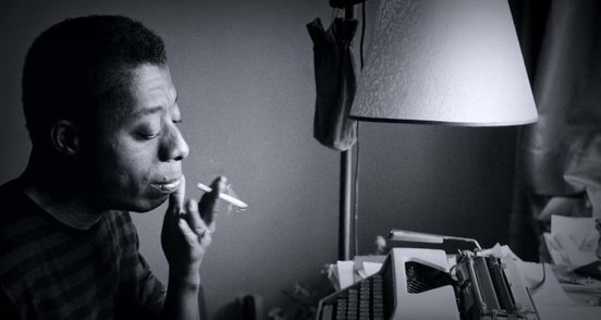 James Baldwin smoking and sitting at a typewriter.jpg