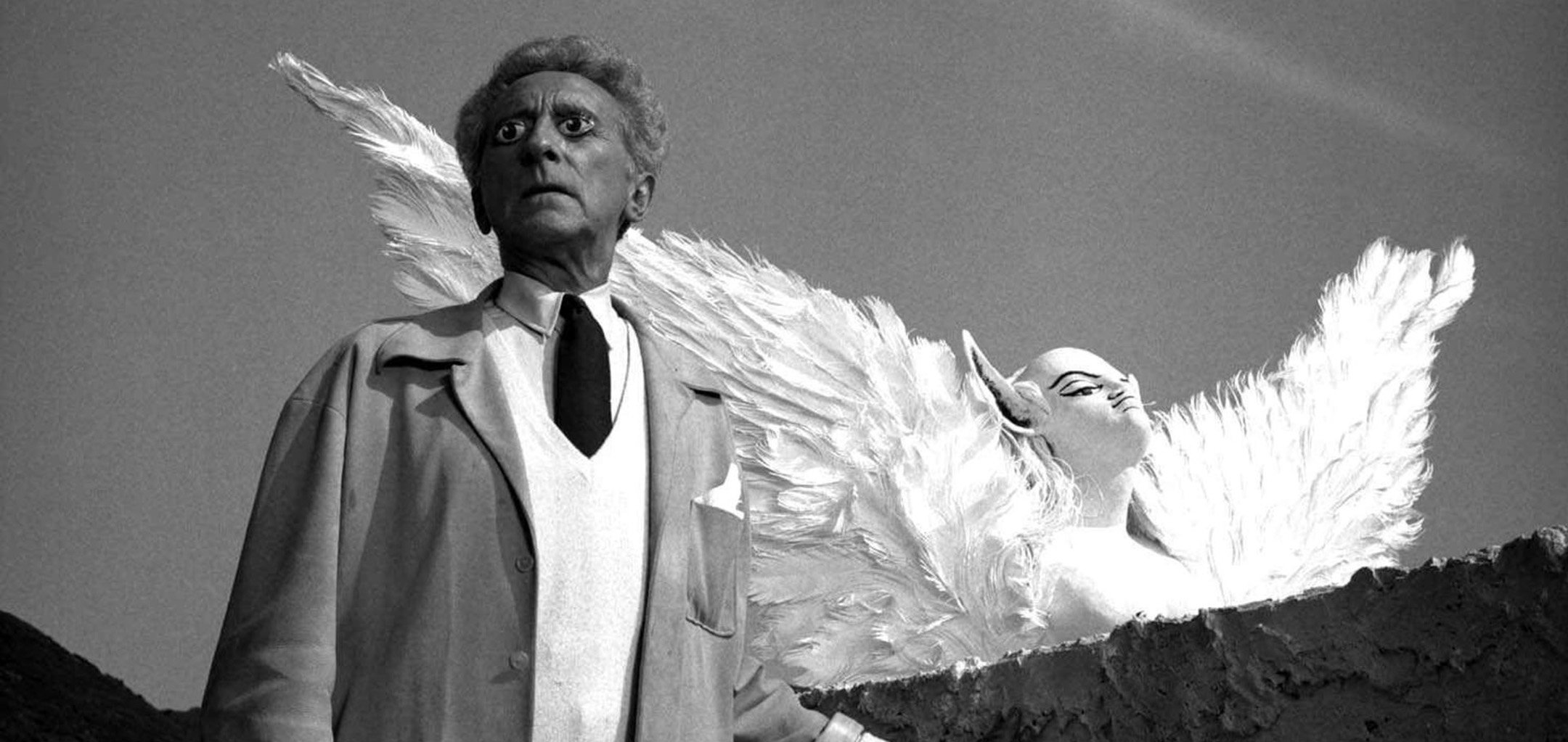 Jean Cocteau with painted eyes and an angel in the background in a still from 'Le Testament D'Orphée' (1960)