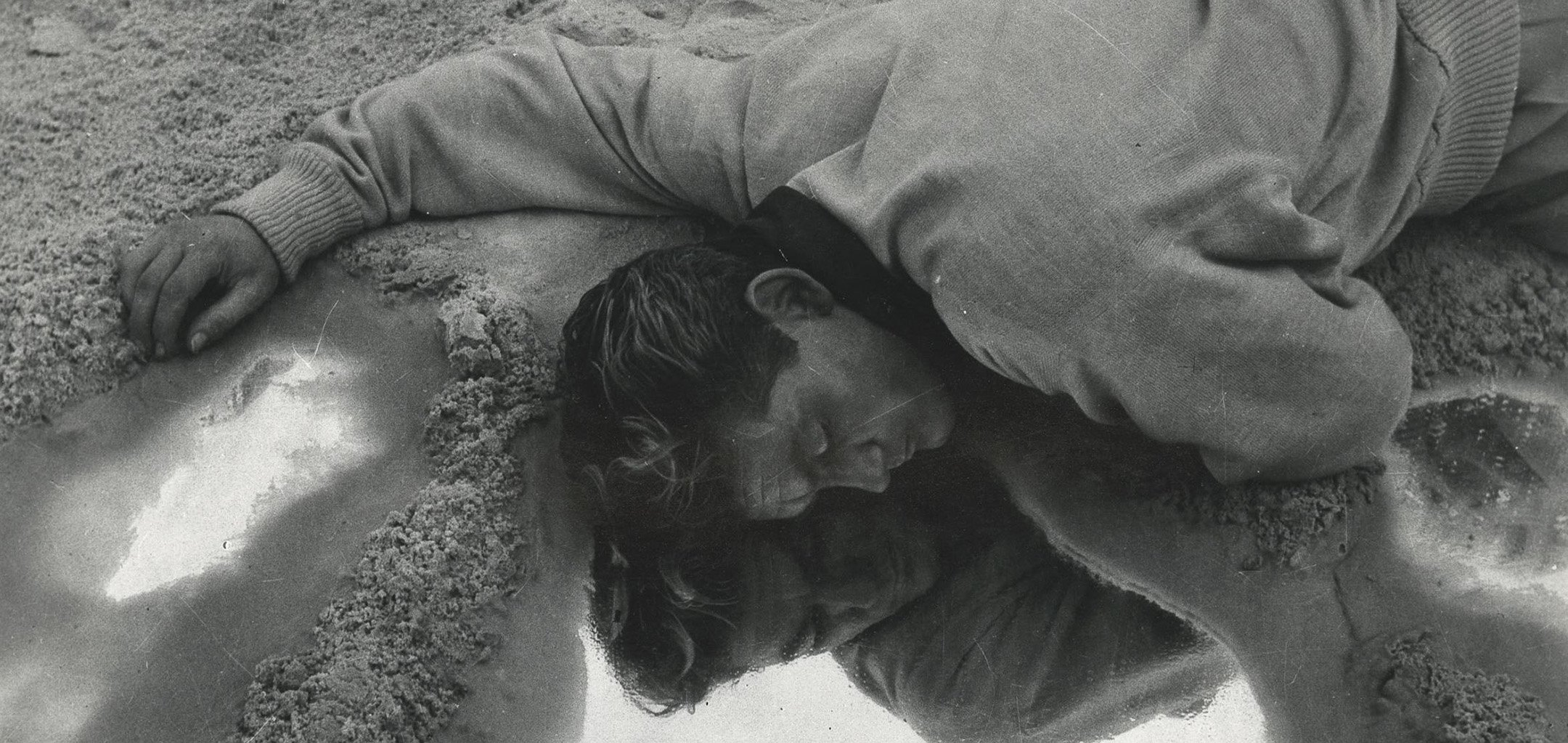 Jean Marais lying facedown in a puddle in a still from Orphée (1950)
