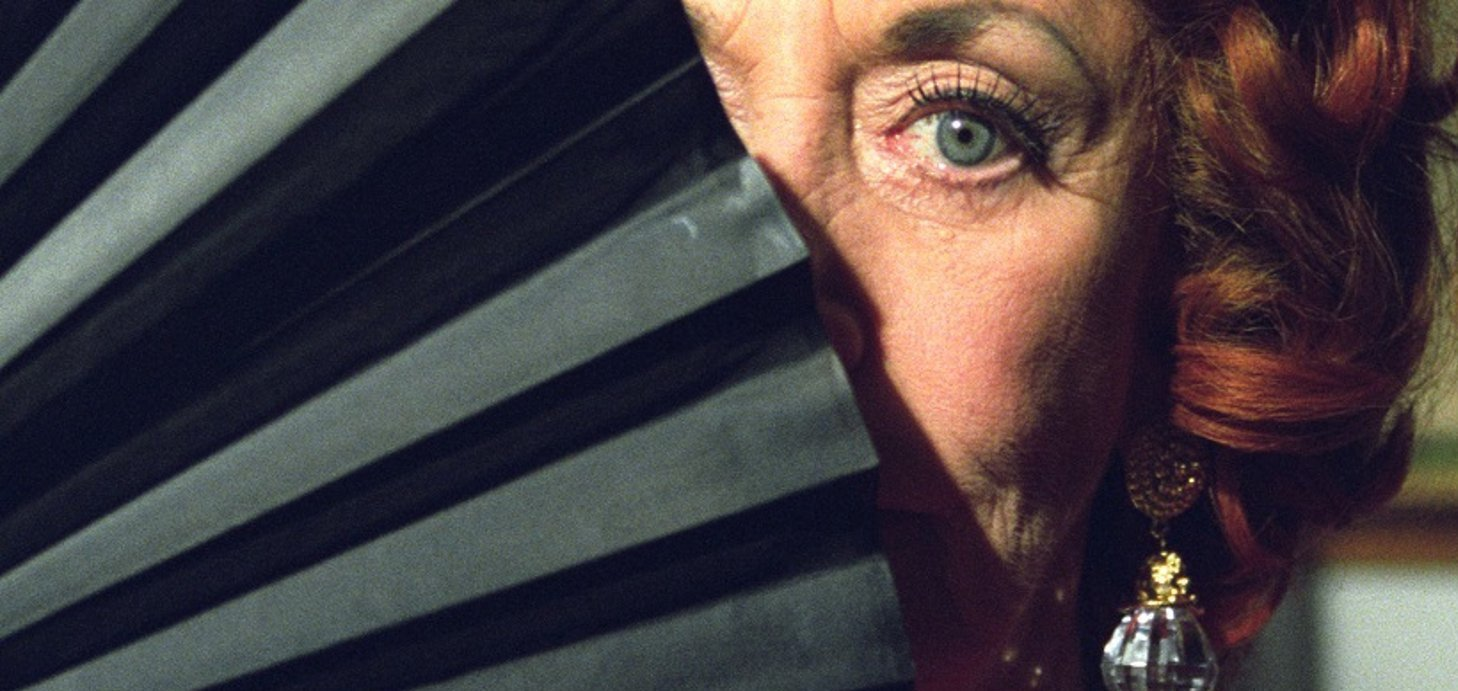 Judi Farr in a still from Unfolding Florence: The Many Lives of Florence Broadhurst (2006), one eye peeking out behind a fan