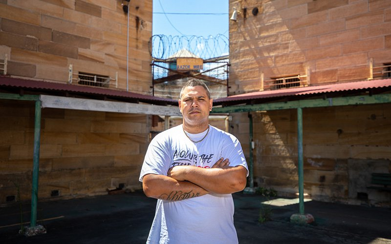 Keenan Mundine stands outside a prison in a still from 'Incarceration Nation' (2021, courtesy (incarcerationnation.com.au)