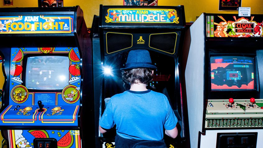 Kid wearing a hat playing Atari Millipede in a games arcade( image courtesy Andrew Cline, Alamy)