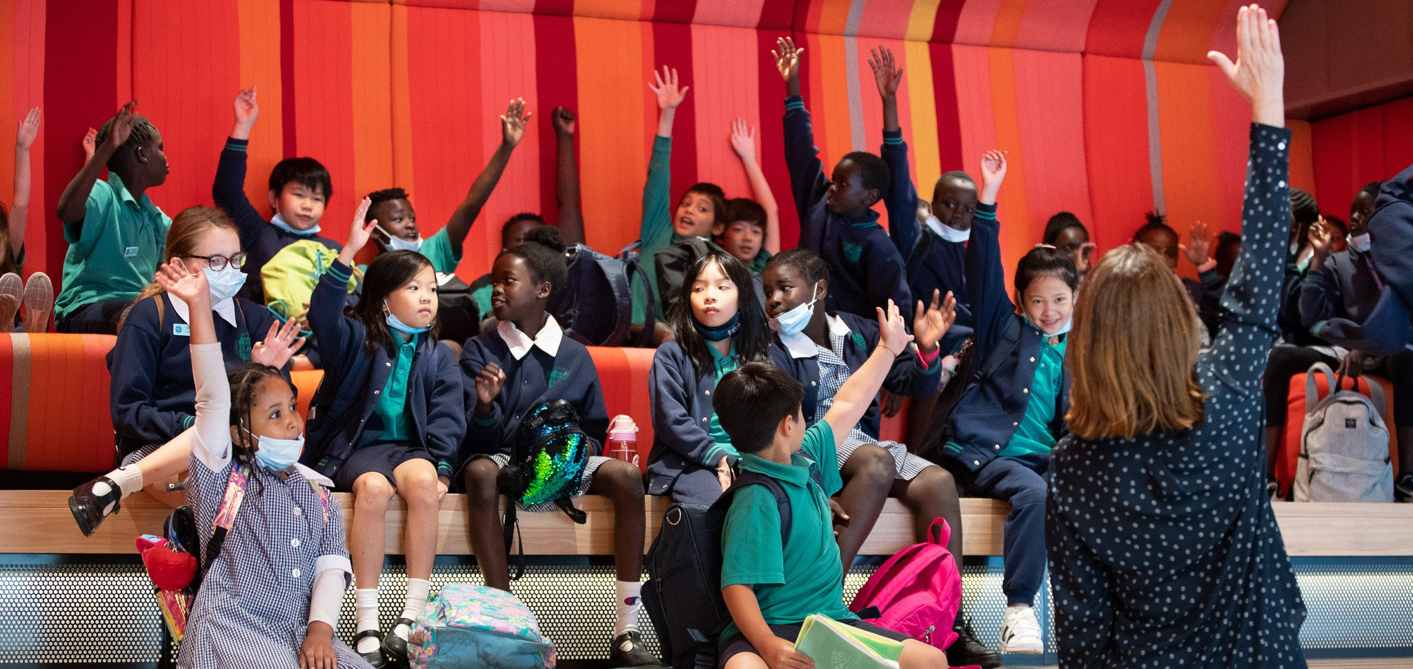 Kids raising their hands in the urban lounge in the ACMI Lightwell