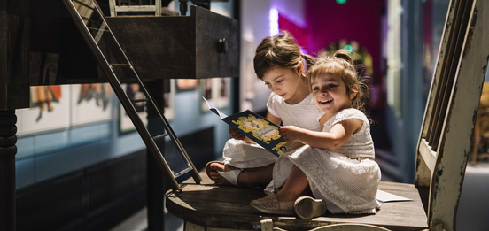 Kids sit on an oversized chair in ACMI's Wonderland exhibition - hero image