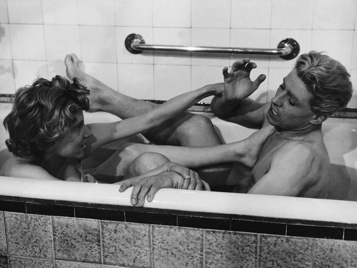 Edouard Dermithe and Nicole Stéphane playfight in a bathtub in a still from 'Les Enfants Terribles' (1950)