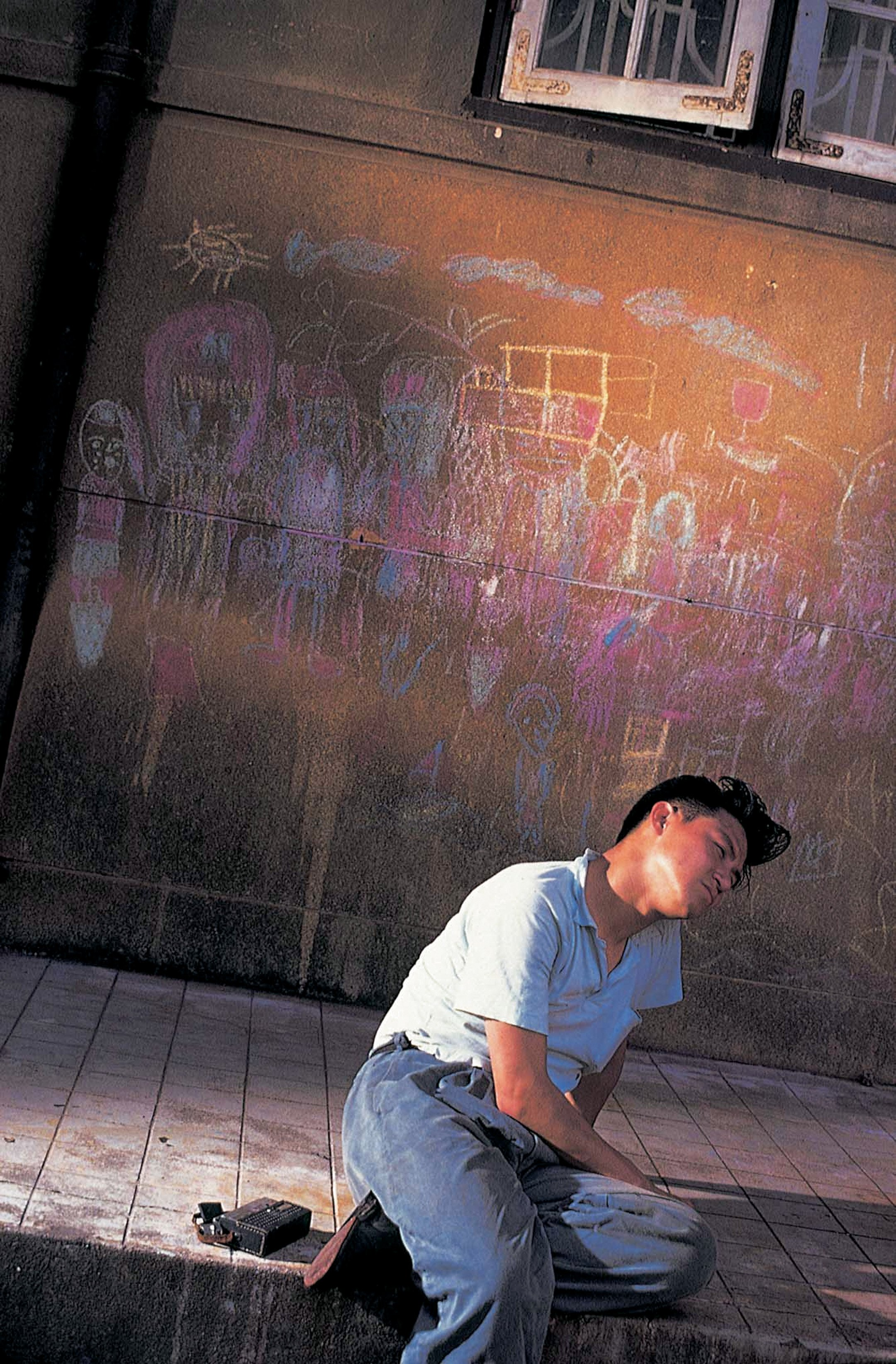 Leslie Cheung in Days of Being Wild - sitting in front of a walk with chalk drawings.jpg