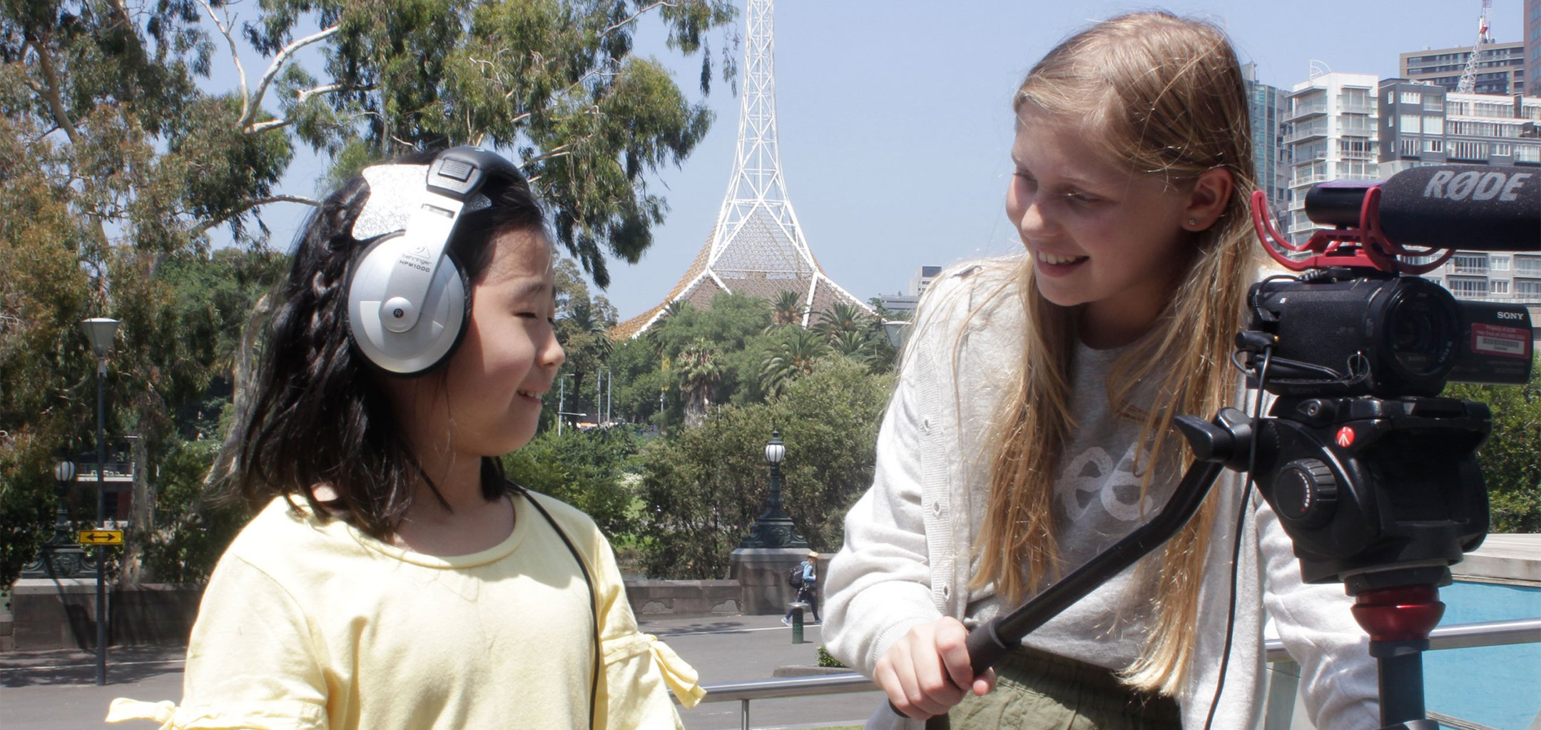 Two young girls operating camera equipment outside the Arts Centre in Melbourne